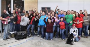 Employees enjoy a show by the company band 5 Second Rule in the new manufacturing space.