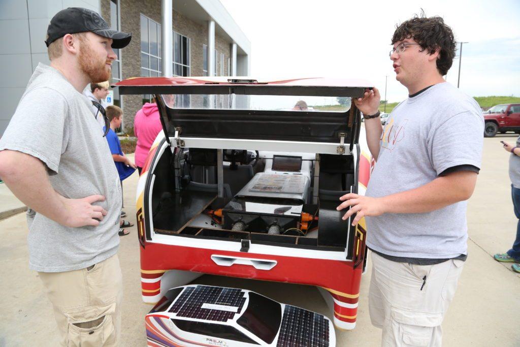 Todd listens as an ISU student explains how the solar car operates.